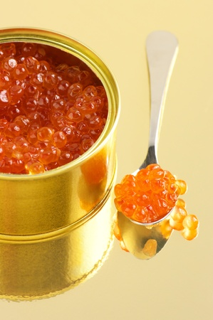 Canned salmon caviar with spoon on golden background. Stock Photo - 11205095