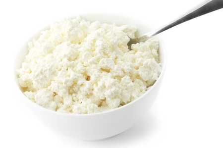 Cottage cheese with spoon in white bowl isolated on white background. Stock Photo