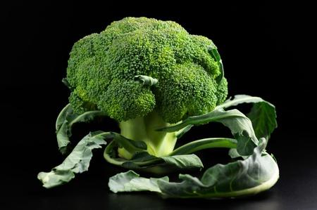 �broccoli: Br�coli crudo con hojas sobre fondo negro. Foto de archivo