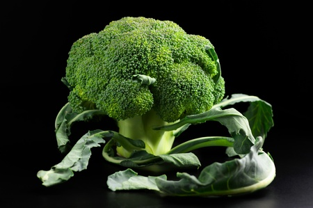 Raw broccoli with leaves on black background.