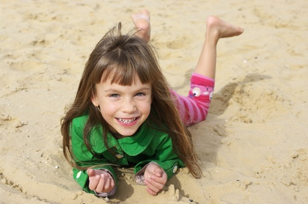 Small cute girl lying on sand at beach. photo