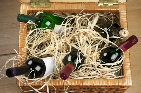Picnic basket with bottles of red and white wine in straw. photo