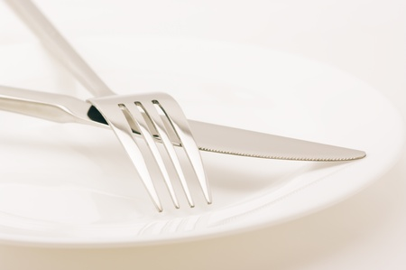 Knife and fork in white plate on light background. Toned image. photo