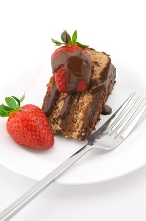 Slice of chocolate cake with strawberries and fork in white plate on white background. photo