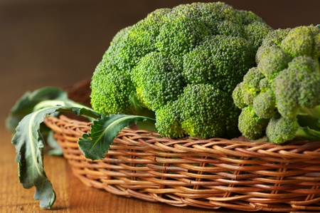 Close-up of raw broccoli in wicker basket on wooden surface. Stock Photo