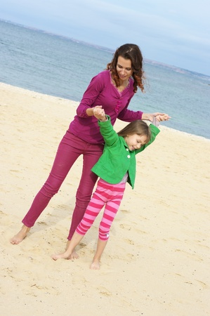 Happy mother and daughter playing at beach. photo