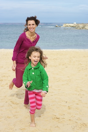 Happy mother and daughter running at beach. photo