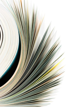 Close-up of magazine pages on white background. Shallow DOF, focus on edges. Stock Photo