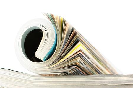 Rolled magazine on magazines stack. Toned image. Stock Photo