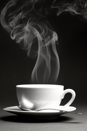 Cup of hot coffee with steam on dark background. Monochrome image. Stock Photo