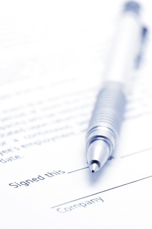 Close-up of silver pen on employment agreement. Selective focus on top of pen. Toned image. photo