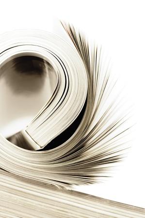 journalism: Close-up of rolled magazine on white background. Toned image.