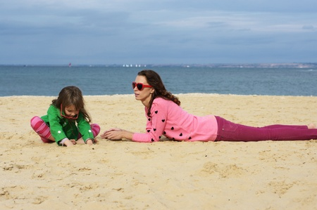 Happy mother and daughter lying at beach. photo