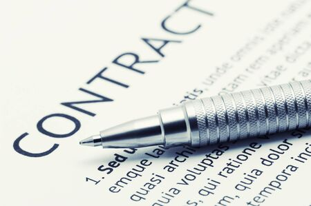 legal document: Close-up of silver pen on contract. Toned image.