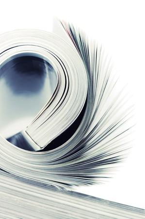 toned image: Close-up of rolled magazine on white background. Toned image.