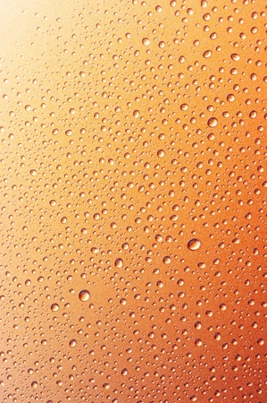 Close-up of water drops on textured metallic surface as background. photo