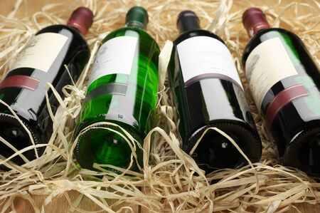 Close-up of four various wine bottles lying in row on straw. Stock Photo - 12373659