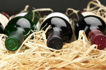 brown bottle: Close-up of three various wine bottles lying on straw.