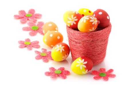 Yellow, orange and red Easter eggs in pot and floral decorations on white background. photo