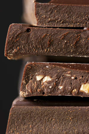 Close-up of stacked assorted dark chocolate on black background  photo