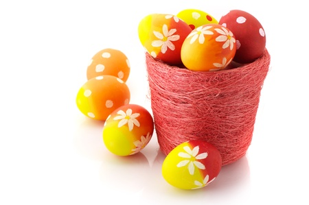 Yellow, orange and red Easter eggs in pot on white background. Stock Photo