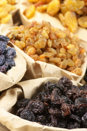 Close-up of various raisins in paper bags. Focus on foreground. photo