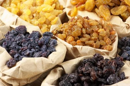 Various raisins in paper bags. Full frame. photo