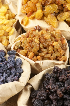 Various raisins in paper bags. Full frame. photo