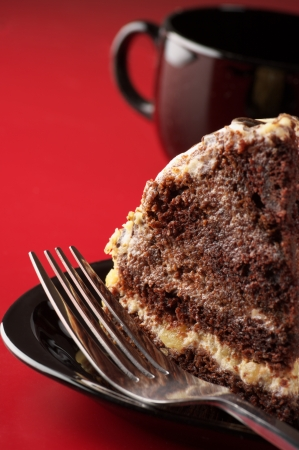 Piece of chocolate cake with fork on black plate and coffee against red background. photo