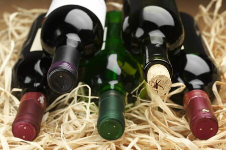 Stack of various wine bottles lying on straw. Stock Photo - 13916602