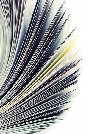 Close-up of magazine pages on white background. Shallow DOF, focus on edges. Stock Photo