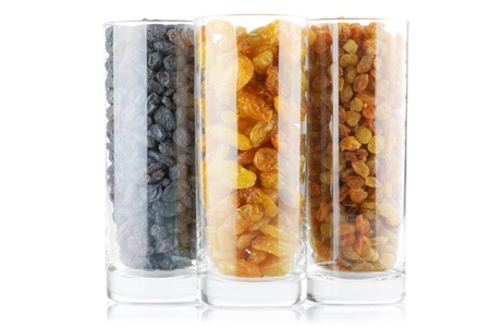 Assorted raisins in glasses isolated on white background. photo