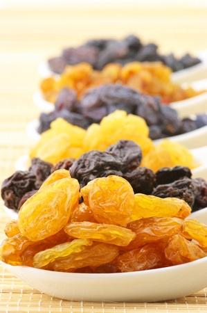 Close-up of various raisins in white ceramic spoons. photo
