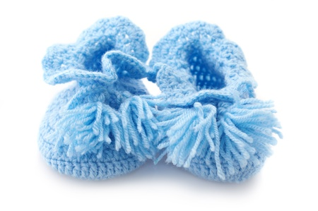 Blue handmade baby's bootees isolated on white background. photo