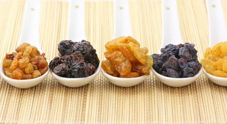 Various raisins in white ceramic spoons on mat. photo