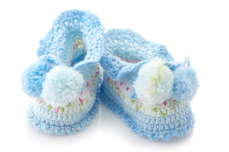 Blue handmade babys bootees isolated on white background.