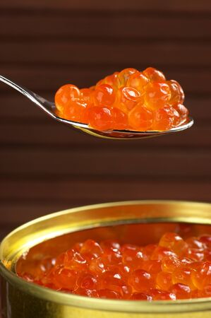 Canned salmon caviar with spoon close-up on brown background. photo