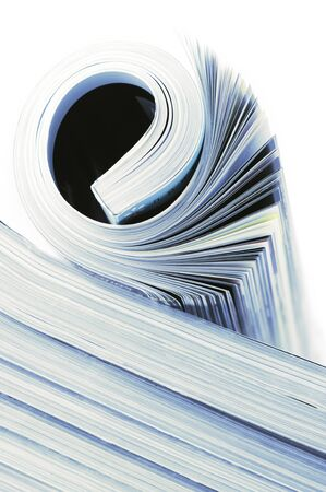 Rolled magazine on magazines stack. Toned image. photo