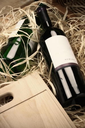 Two wine bottles lying in wooden box with straw. photo