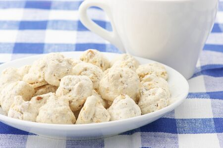 Almond cookies in white plate and white cup on checkered tablecloth. photo