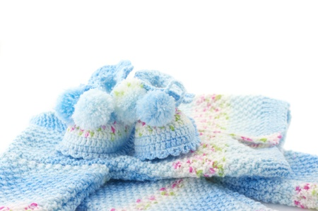 Handmade babys knitted clothes on white background.