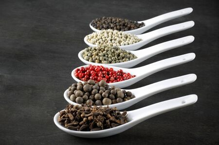 Assorted pepper and clove in white spoon on black wood. photo