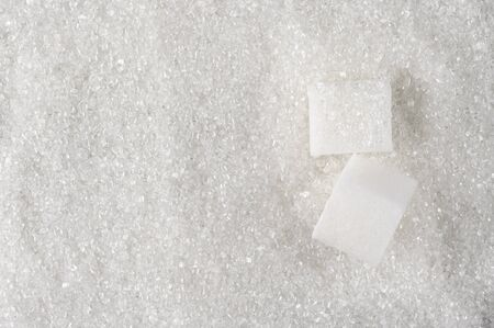 Granulated sugar and sugar cubes as background. photo
