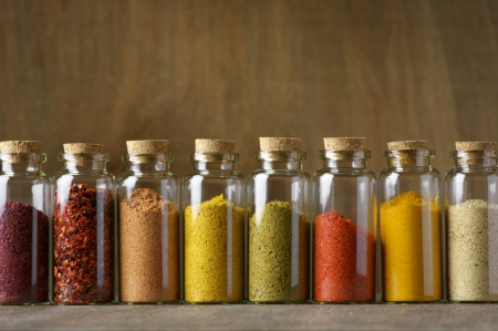 Assorted ground spices in bottles on wooden background. photo