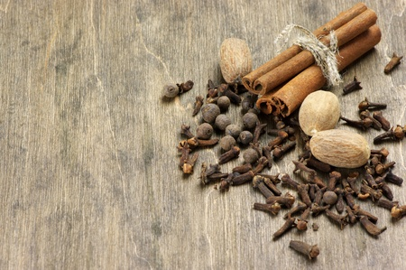 Cinnamon, nutmeg, allspice and cloves on wooden background. Top view point. photo