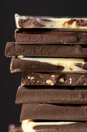 Close-up of stacked assorted chocolate on black background. photo