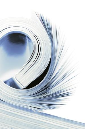 Close-up of rolled magazine on white background. Toned image.