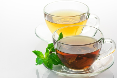 Cups of black and green tea with mint on white background. photo