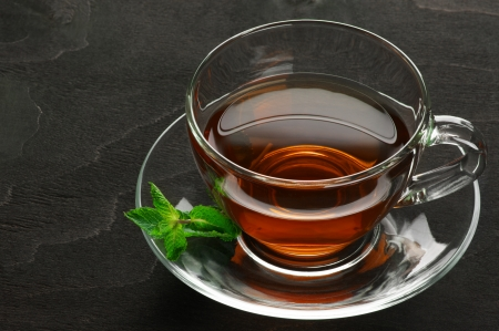 Glass cup of tea with mint on dark wood. photo