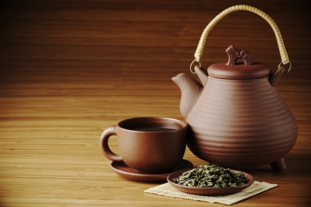 Dried tea, cup of tea and teapot on wooden background with copy space.